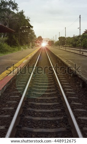 "view of the length of railway with pavement at left and right side of railway,filtered image, light effect and flare added,selective focus,mean ""Theres light at the end of the tunnel"", success way - stock photo"
