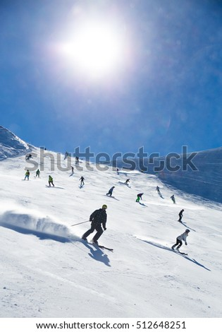 view of the mass of people skating on a ski slope in the mountains at ski resort