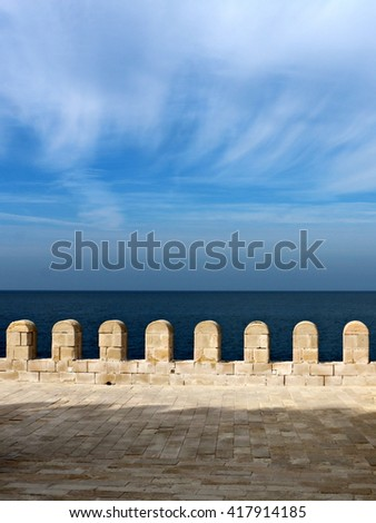 View of the Mediterranean Sea through the citadel ramparts with wispy clouds.