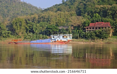 View of the Mekkong in Laos - boats and houses on the river - stock photo