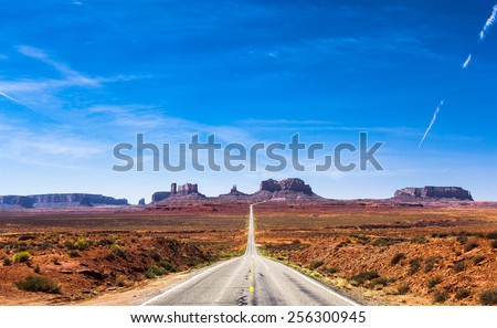 View of the Monument Valley and the highway 163 in Utah during a beautiful summer day. Vivid blue sky against the colorful desert and the rocks. The road is vanishing in the Monument Valley. - stock photo