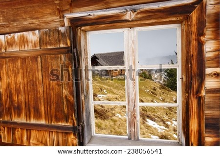 View of the mountain hut through the wooden windows - stock photo