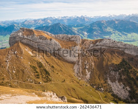 View of the mountain range on the hiking path towards Pilatus (a famous peak of swiss alps in Lucerne), above the Lucerne lake in Switzerland,with numerous snow covered peaks of the alps in background - stock photo