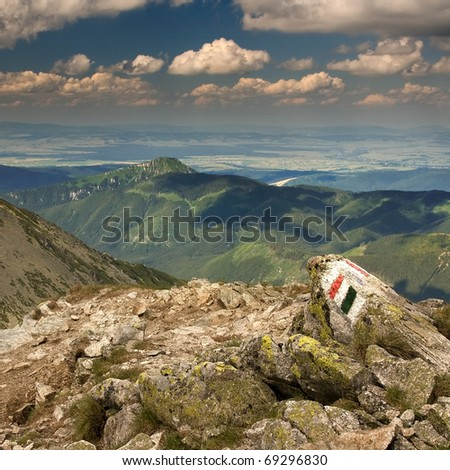 View of the mountains from the path with a mark of tourist trail on the rock. Rohace in Slovakian Western Tatra Mountains. - stock photo