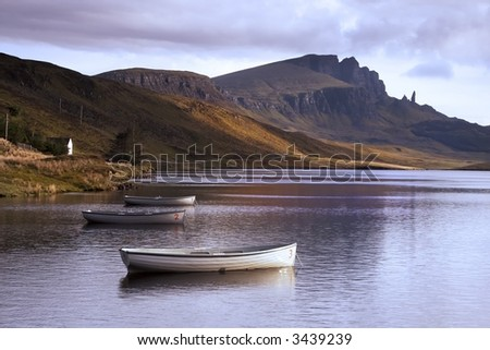 View of the Old Man of Storr over Loch Leathann in the Isle of Skye. Warm dawn sunlight lights the sides of the distant mountain which reflects in the calm, still waters of the Loch - stock photo