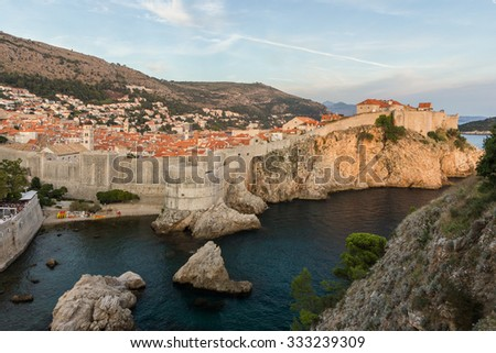 View of the Old Town and City Walls on a steep cliff in Dubrovnik, Croatia, at sunset. - stock photo