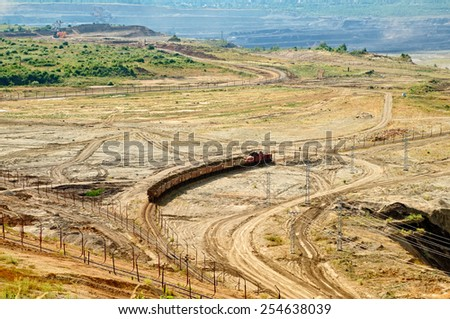 View of the open-pit mine, mining train carrying excavated materials at the forefront, mining machines in the background in the distance, view from above - stock photo