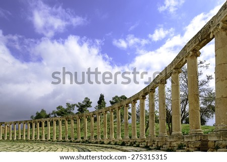 View of the Oval Forum colonnade in ancient Jerash, Jordan - Jerash is the site of the ruins of the Greco-Roman city of Gerasa, one of the best preserved Roman cities in the Middle East. - stock photo