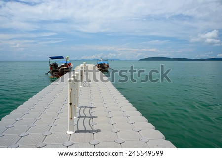 View of the pier, boats and island, summer sunny day - stock photo