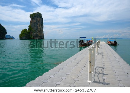 View of the pier, boats and rocky island, summer sunny day - stock photo