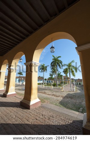 View of the Plaza Mayor between archways in the portico of historic colonial architecture in  Trinidad, Cuba - stock photo
