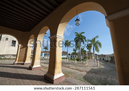 View of the Plaza Mayor between archways in the portico of the historic colonial architecture of the Palacio Brunet in the UNESCO heritage center of Trinidad, Cuba - stock photo