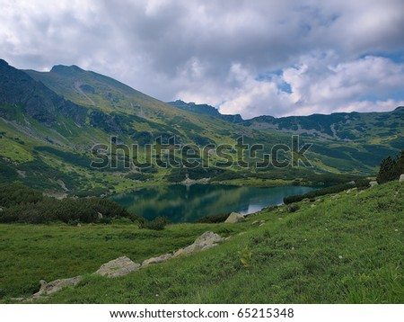 View of the pond, and peak in the Western Tatras. In the background hostel Kasprowy Wierch, Poland. - stock photo