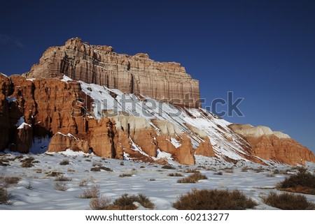 View of the red rock formations in Goblin Valley with blue sky?s and clouds and snow on the ground