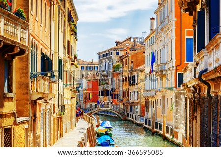 View of the Rio Marin Canal and the Ponte Cappello dei Garzoti from the Ponte de la Bergami in Venice, Italy. Colorful facades of old houses. Venice is a popular tourist destination of Europe. - stock photo
