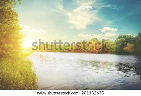 View of the river with green coast and clouds and bright sun - stock photo