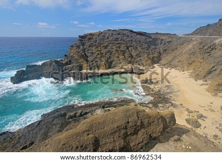 View of the rock walls and sands of Halona Beach Cove near Honolulu on the southeast coast of the Hawaiian island of Oahu - stock photo