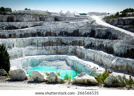 View of the rocky layers of a large and impressive open pit white marble stone mine. - stock photo