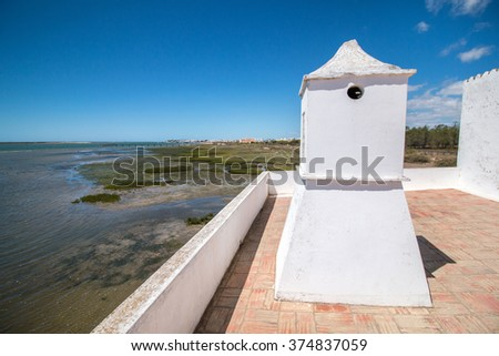 View of the rooftop of a house with white chimney to Ria Formosa marshlands in Portugal. - stock photo