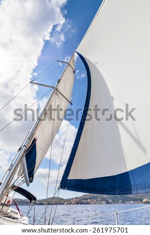View of the sails and mast tilt in the wind. View of the sails and mast tilt in the wind against the background of the coast on a sunny day. Mallorca, Spain - stock photo