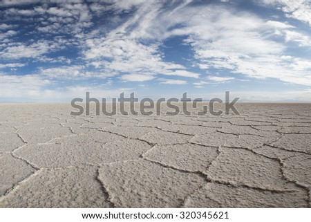 View of the Salar of Uyuni against a blue sky during the dry season, the salt plains are a completely flat expanse of dry salt. Bolivia - stock photo