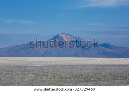 View of the Salar of Uyuni against a blue sky during the dry season with very low angle, the salt plains are a completely flat expanse of dry salt. Bolivia - stock photo