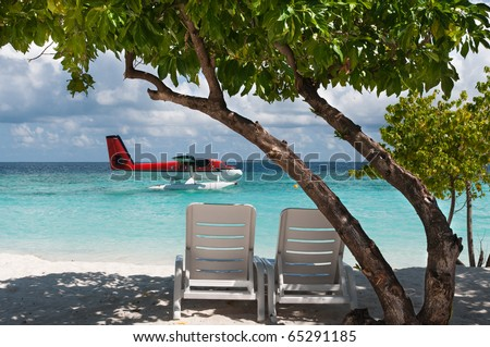View of the seaplane from the tropical beach with two sun chairs. - stock photo