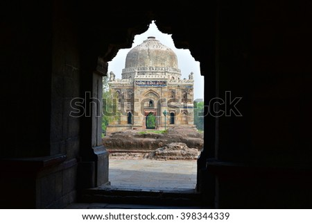 View of the Shisha Gumbad or Dome framed within an arched gateway of main tomb, Ancient Mughal Architecture in India, Lodhi Gardens, New Delhi - stock photo