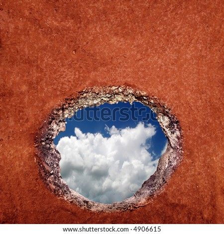 View of the sky as seen from under a hole in the ground. - stock photo