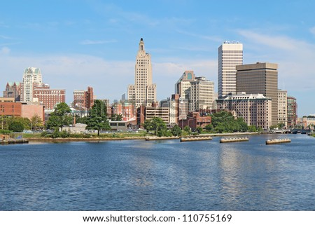 View of the skyline of Providence, Rhode Island, from the far side of the Providence River against a blue sky and white clouds - stock photo