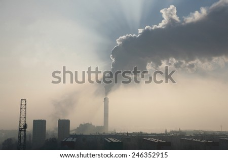 view of the smoky chimney of power plant with blocks of flats on the first plan, all in grey colors - stock photo