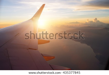View of the sunset,clouds and airplane wing from the Inside - stock photo