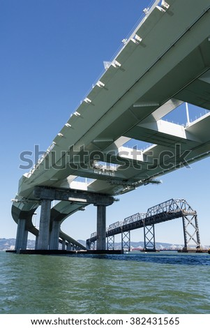View of the superstructure of the new San Francisco Bay Bridge with old bridge in background from water