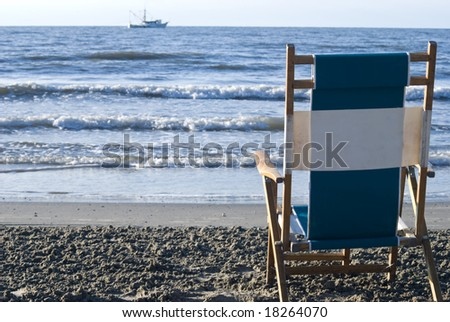 View of the surf from behind a single beach chair with a fishing boat in the distance. - stock photo