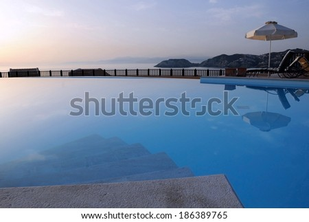 View of the swimming pool and the sea and sky in the background on Crete island in Greece at sunrise. - stock photo