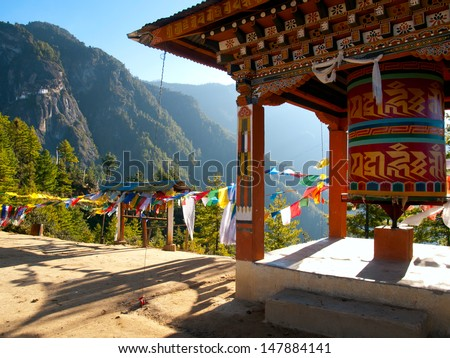 View of the Taktshang monastery in Paro (Bhutan) with prayer flags and a prayer wheel in the front - stock photo