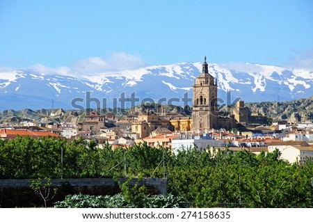View of the town and Cathedral with the snow capped mountains of the Sierra Nevada to the rear, Guadix, Granada Province, Andalucia, Spain. - stock photo