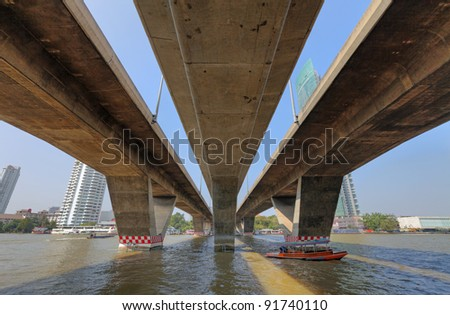 View of the triple concrete ramp of Taksin Bridge crossing the Chao Phraya River from the Sathorn Taksin ferry pier. This is a HDR image. - stock photo