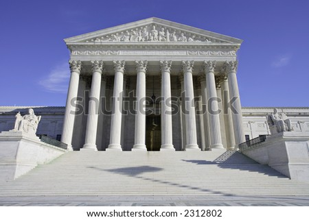 View of the United States Supreme Court building with shadow of flag on the steps. - stock photo