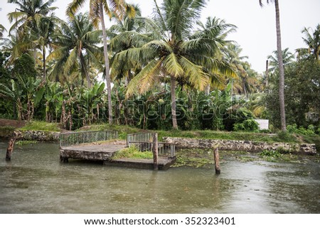 View of the Vembanad lake and the lush green banks in Kottayam. Tall green trees are seen on the banks along with the clear white sky on a sunny day. - stock photo