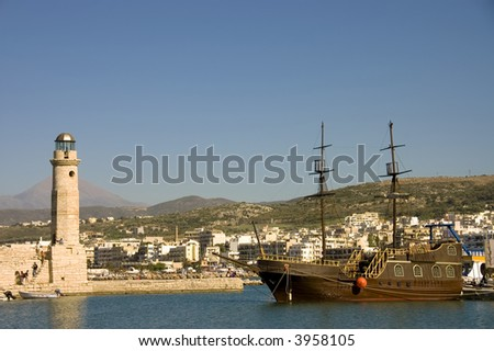 View of the venetian harbor of Chania, Crete, Greece with  lighthouse and its typical greek schooner - stock photo