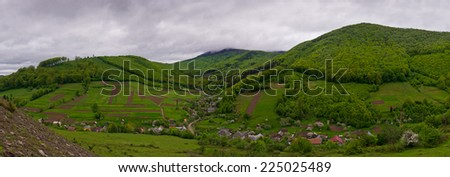 View of the village in a mountain area. Green hills. Cloudy. Ukrainian Carpathians