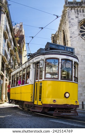 View of the vintage famous yellow electrical trams circulating still today in Lisbon, Portugal. - stock photo