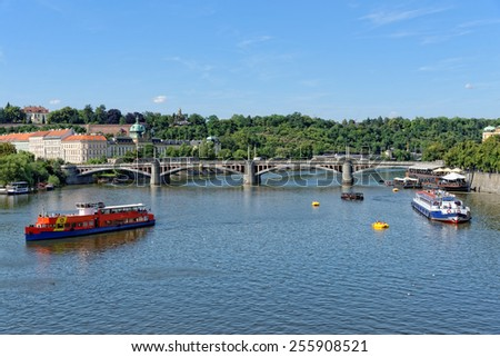 View of the Vltava river with cruise tour boats from the Charles Bridge. The Charles Bridge is a famous historic bridge that crosses the Vltava river in Prague, Czech Republic. - stock photo