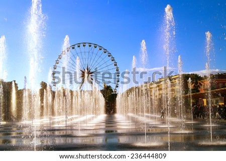 View of the water jets in the city of Nice (French Riviera) during Christmas holidays.The Ferris wheel is in the back ground.