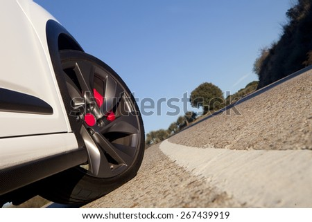 View of the wheel of a withe sport car on a road with blue sky on the background.  Wheel on a road - stock photo