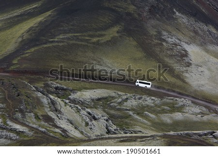 View of the white 4x4 bus from above on a road in highlands among green moss, Iceland - stock photo