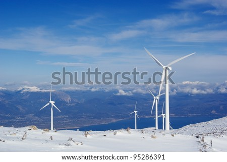 View of the windmills for electricity production on a snowy mountain - stock photo