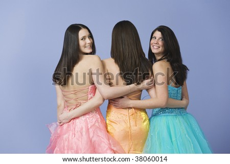 View of three teenage girlfriends holding each other by the waist while wearing prom dresses. - stock photo