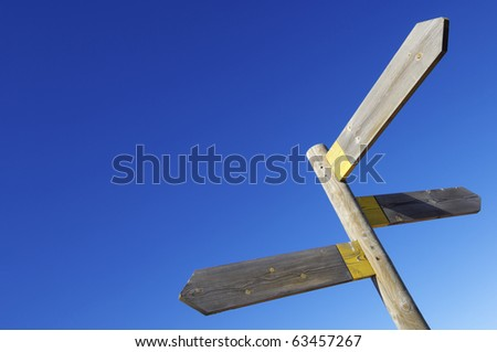 view of three wooden directional signs on a pole - stock photo